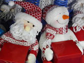 Christmas snowman and Santa Claus with red gift boxes. — Stock Photo