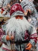 Un juguete de santa claus con un saco lleno de regalos cerca del árbol de navidad. — Foto de Stock