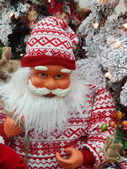 A toy Santa Claus with a sack with presents near the Christmas tree. — Stock Photo