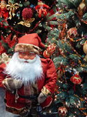 A toy Santa Claus with a lantern and a sack with gifts near the Christmas tree. — Foto Stock