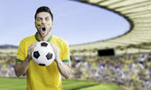 Brazilian soccer player holding a soccer ball celebrates on the stadium — Stock Photo