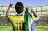 Brazilian soccer player holding the flag of Brazil celebrates with the fans on the stadium — Photo