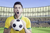 Brazilian man holding a soccer ball celebrates on the Arena background — Photo