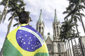 Brazilian holding a brazilian flag looks to Se Cathedral in Sao Paulo, Brazil — Photo