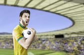 Brazilian fan holding a ball celebrates on the stadium — Stockfoto