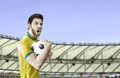 Brazilian soccer player holding a ball celebrates with the fans on the stadium — Stock Photo