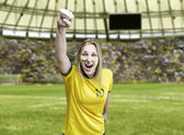 Brazilian fan celebrates on the stadium with her face painted — Foto de Stock