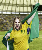 Brazilian fan celebrates on the stadium with her face painted — Stock Photo