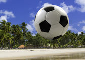 Soccer ball traveling on the beach — Stock Photo