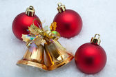 Bells and red Christmas balls on snow — Stock Photo