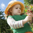 The little girl with wild strawberry - Stock Photo