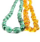 Malachite and amber beads on the white — Stock Photo