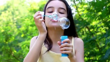 Teenager blowing colorful bubbles soap — Stockvideo