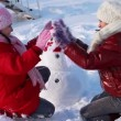 Happy girls with snowman — Stock Video #26380911