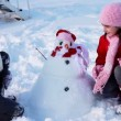 Happy girls with snowman — Stock Video