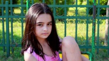 Sad young girl on swing — Stock Video