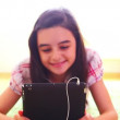 Smiling girl listening to music on digital tablet pc — Stock Video