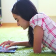 Stock Video: Smiling girl listening to music on digital tablet pc