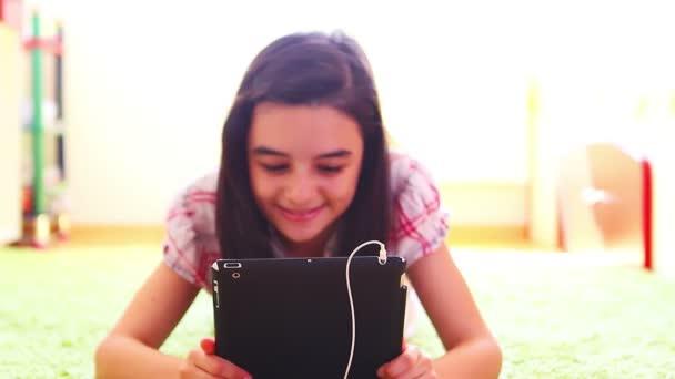 Jeune fille souriante, écouter de la musique sur pc tablette numérique — Vidéo