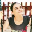 Teenage girl on swing smiling at camera — Stock Video