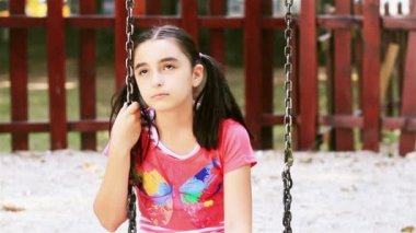 Sad young girl sits on swing — Stock Video