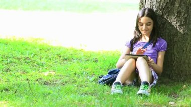 Teenage girl using digital tablet in park — Αρχείο Βίντεο