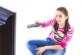 Happy little girl laying down and watching tv — Stock Photo