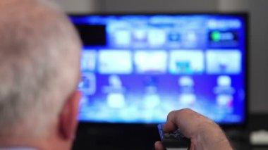 Smart tv and senior man hand pressing remote control — Stock Video