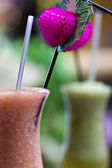Two colourful alcoholic cocktails and a pink umbrella — Stock Photo