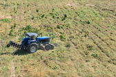Farmer working with tractor plow the fields — Stock Photo