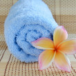Blue towel and plumeria flower on wooden background — Stock Photo
