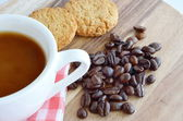 Coffee beans and cup with cookies on wooden background — Stock Photo