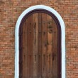 Arch wooden door with brick building — Stock Photo
