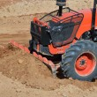 Orange tractor in construction site — Stock Photo #49198709