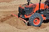 Orange tractor in construction site — Stock Photo