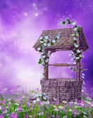 Wishing well on a colorful meadow — Stock Photo