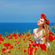 Girl walking in poppy field — Stock Photo