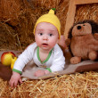 Baby boy in a fun pear hat is in the hayloft — Stock Photo