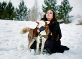 Woman with dog in snow — Stock Photo