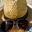 Hat and sunglasses on the beach. - Stockfoto