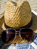 Hat and sunglasses on the beach. — Stock Photo