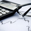 Stock Photo: Chart, calculator, glasses as financial stock analysis concept