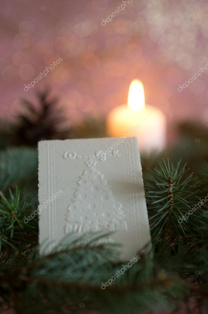 Christmas wafer on spruce branches, background candle — Stock Photo #14492635