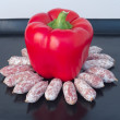 Red peppers with sharp, maturing sausages, the stoneware tray — Stock Photo