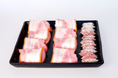 Spicy, aged sausages and bacon pieces on stoneware tray — Stock Photo