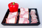 Red peppers with sharp, maturing sausages and bacon, for stoneware tray — Stock Photo