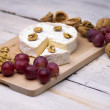 Cheese, walnuts, grapes — Stock Photo