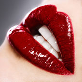 Beautiful female with red shiny lips close up — Stockfoto