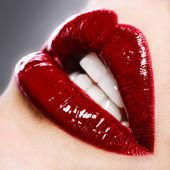 Vacker kvinna med röda blanka läppar på nära håll — Stockfoto