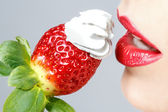 Beautiful red lips and tasty strawberry whipped cream — Stock Photo